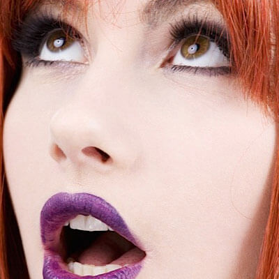 woman with red hair and purple lipstick gasping