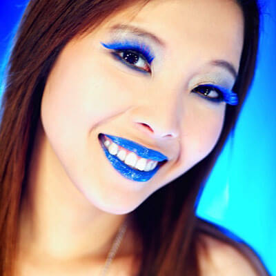 woman with blue lipstick and blue eyelashes smiling at the camera